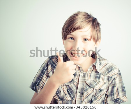 little boy thumbs up on gray background - stock photo