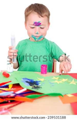 little boy tinkering with colored paper, glue and paint