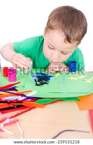 little boy tinkering with paint and colored paper