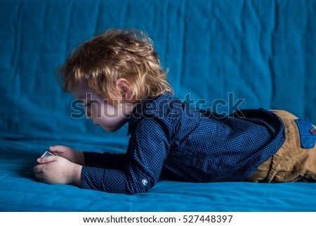 little boy toddler  lying on the couch and watching plays in the smartphone