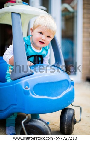 Little boy toddler playing in toy car