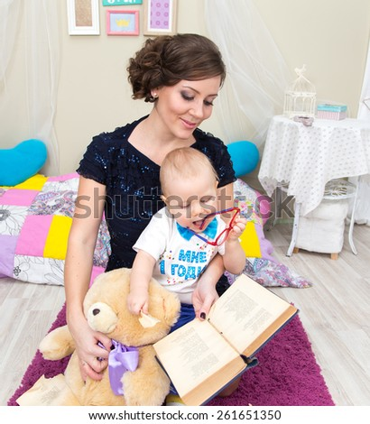 Little boy together with his mother and teddy bear read a book - stock photo