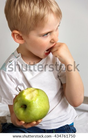 Little boy touching the hands of the teeth that come out, the child is eating a green apple on a white background, soft focus - stock photo