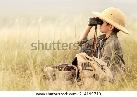 Little boy tourist looking into the distance with binoculars through the thick grass - stock photo