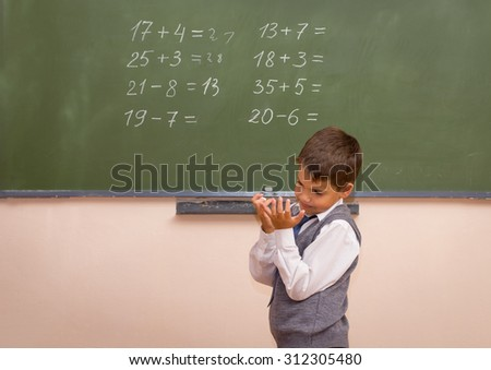 Little boy trying to solve arithmetical standing at the chalkboard. - stock photo