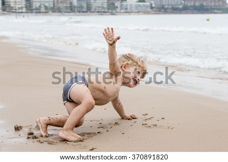 Little boy trying yoga on the beach.