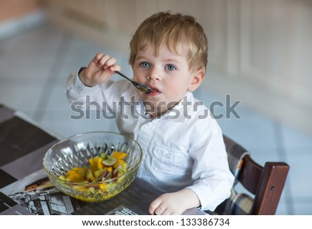 Little boy two years old eating fruit salad indoor - stock photo