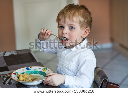 Little boy two years old eating pasta indoor - stock photo