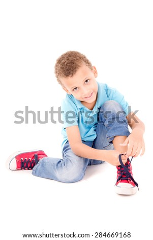 little boy tying his shoes isolated in white
