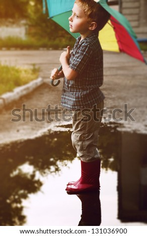 Little boy under bright umbrella after summer rain - stock photo