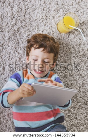Little boy using a pad./ Child playing with digital tablet stretched on a carpet - stock photo