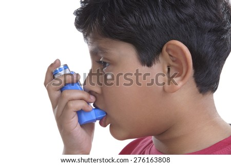 Little boy using an inhaler - stock photo