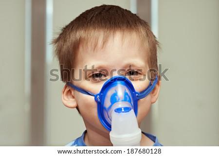 Little boy using an inhaler indoors - stock photo