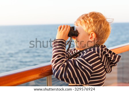 little boy using binoculars while on a cruise ship in open sea - stock photo