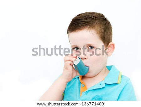 little boy using his asthma pump - stock photo