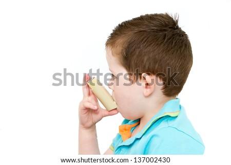 little boy using his asthma pump - stock photo
