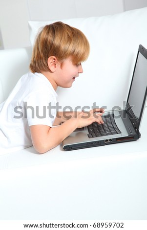 Little boy using laptop computer at home