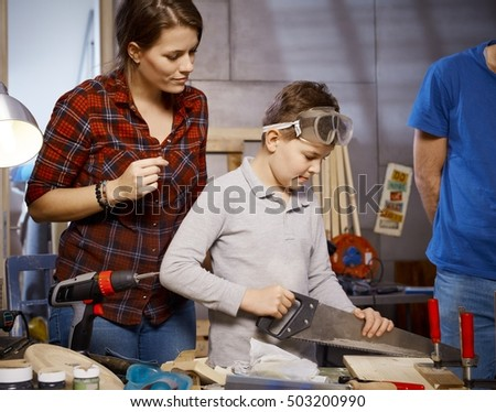 Little boy using saw in workshop, mother watching.