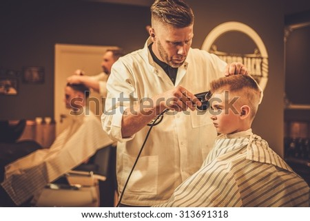 Little boy visiting hairstylist in barber shop - stock photo