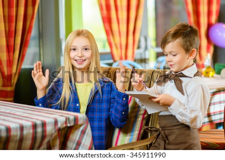 little boy waiter accepts the order in a cafe or restaurant - stock photo