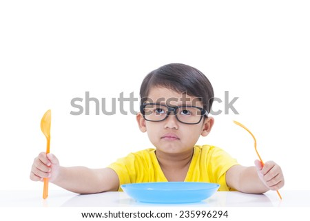 Little boy waiting for food with spoon and fork at table  - stock photo