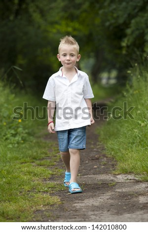 Little boy walking in a path in the woods - stock photo