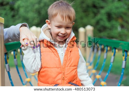 Little boy walking on a log on the playground, mom holding her son's hand. Sunny autumn day.