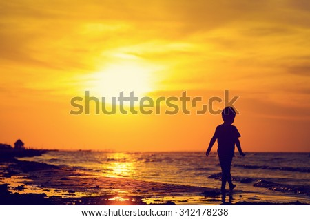little boy walking on sunset beach, family vacation concept