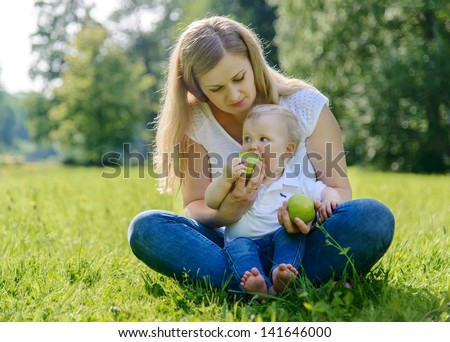 Little boy walking to his mother making his first steps on grass in park, metaphor for beginning of a way
