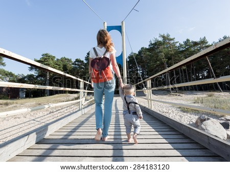 Little boy walking with holding hands with his mom, back view. - stock photo
