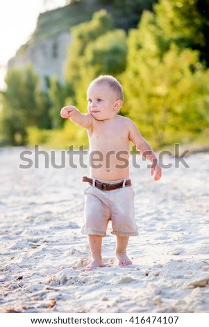 little boy walks on the beach in the summer at sunset