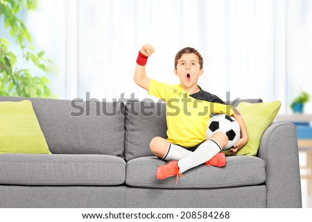 Little boy watching a football match seated on a sofa at home - stock photo