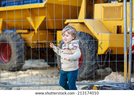 Little boy watching excavator on construction zone, outdoors - stock photo