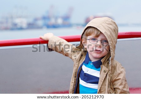 Little boy watching ships on a ferry - stock photo