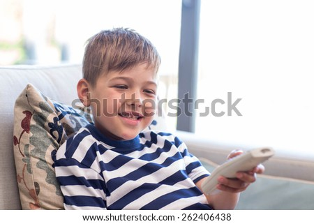 Little boy watching tv on the couch at home in the living room - stock photo