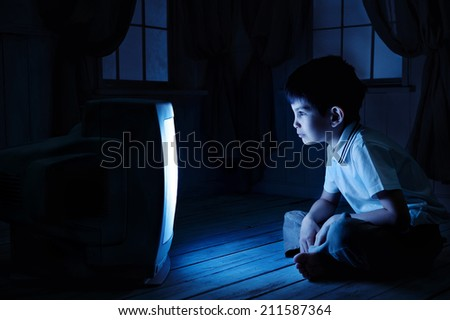 Little boy watching TV one night on the floor - stock photo