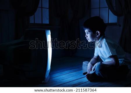 Little boy watching TV one night on the floor - stock photo