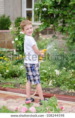 Little boy watering flowers in the garden - stock photo