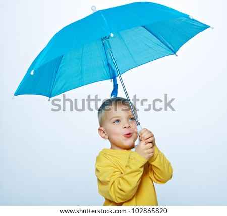 little boy wearing a bright yellow shirt holding a blue umbrella in his hand over a light studio background - stock photo