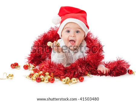 Little boy wearing a Santa hat and playing with baubles. Isolated on white background - stock photo