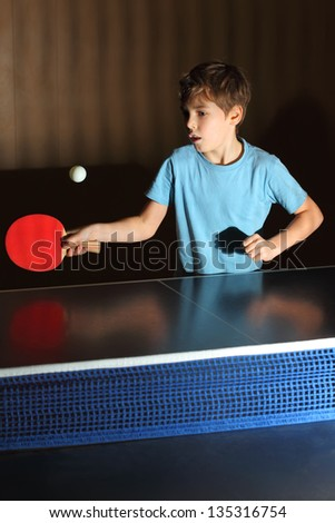 little boy wearing blue shirt playing ping pong; concentrated face; blue net - stock photo