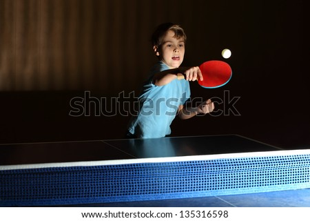 little boy wearing blue shirt playing ping pong; concentrated face; boy stuck out his tongue - stock photo