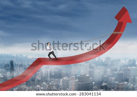 Little boy wearing business suit and pulling arrow upward with a rope above city - stock photo