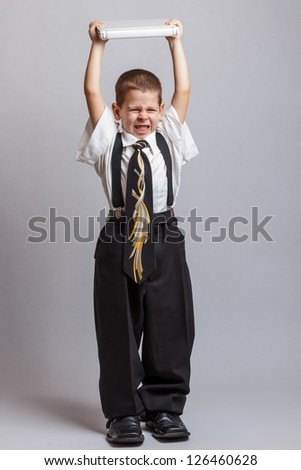 Little boy wearing business suit throwing laptop and want to destroy it - stock photo