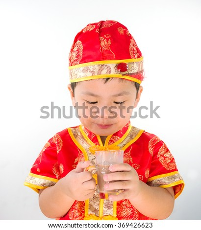 Little boy wearing Chinese New Year suit in studio and choccolate milk on hand, isolate white background,