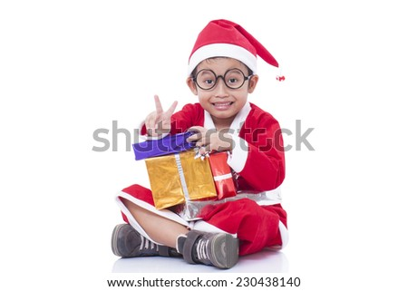 Little boy wearing Santa Claus uniform with gifts and showing victory sign. - stock photo