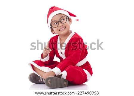 Little boy wearing Santa Claus uniform with pointing up. - stock photo