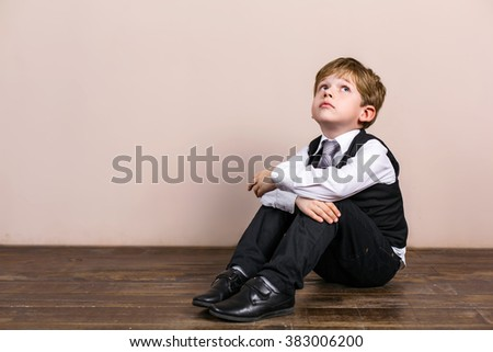 Little boy wearing school uniform. Boy sitting at wooden floor and dreaming - stock photo