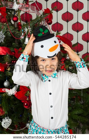 Little boy wearing snowman hat and bow  and standing in front of Christmas tree