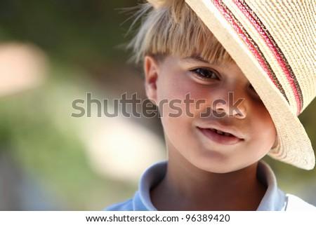 Little boy wearing straw hat - stock photo